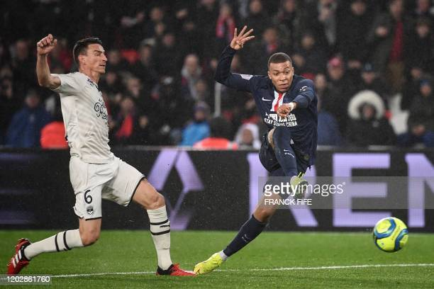 Paris Saint-Germain's French forward Kylian Mbappe shoots the ball next to Bordeaux's French defender Laurent Koscielny during the French L1 football...