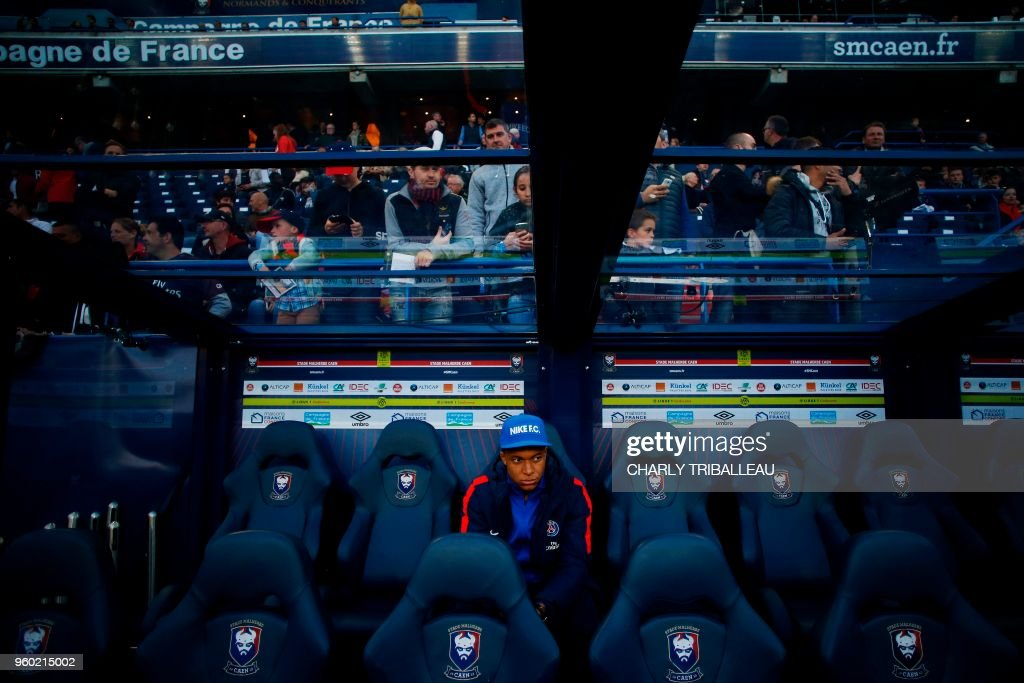 TOPSHOT - Paris Saint-Germain's French forward Kylian Mbappe sits before the French L1 football match between Caen (SMC) and Paris (PSG) on May 19, 2018, at the Michel d'Ornano stadium, in Caen, northwestern France.