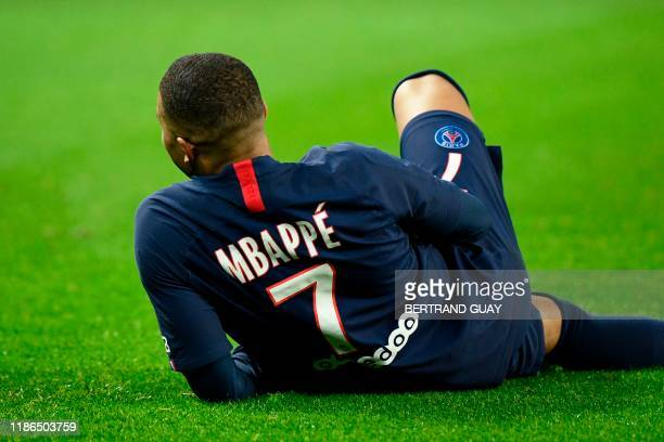 TOPSHOT Paris SaintGermain's French forward Kylian Mbappe sits on the ground as he celebrates after scoring a goal during the French L1 football...