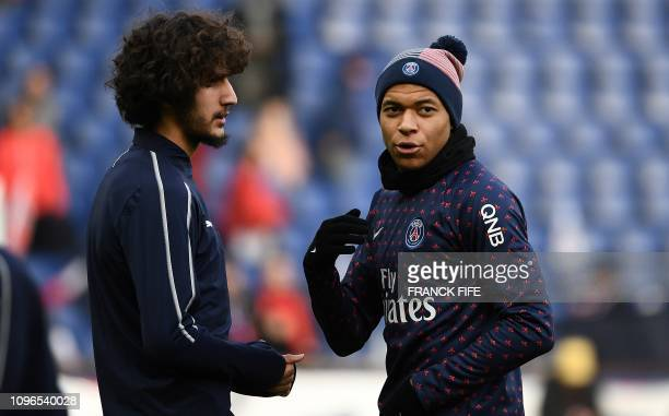 Paris SaintGermain's French forward Kylian MBappe speaks with Bordeaux's midfielder Yacine Adli ahead of the French L1 football match between Paris...