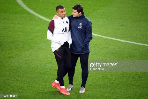 Paris Saint-Germain's French forward Kylian Mbappe talks with Paris Saint-Germain's Argentine coach Mauricio Pochettino during a training session at...