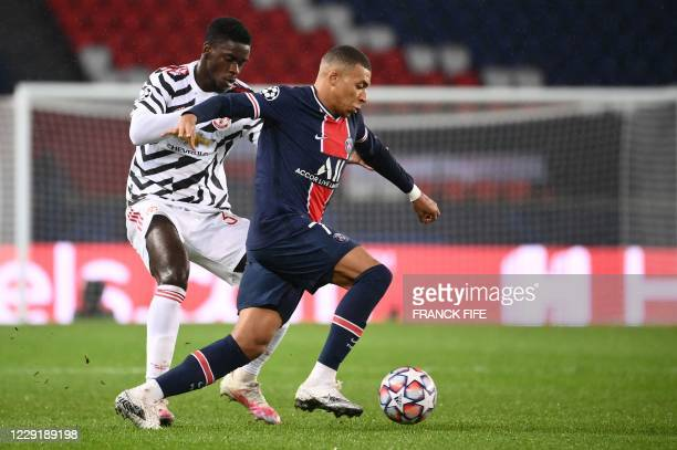 Paris SaintGermain's French forward Kylian Mbappe vies for the ball with Manchester United's English defender Axel Tuanzebe during the UEFA Champions...