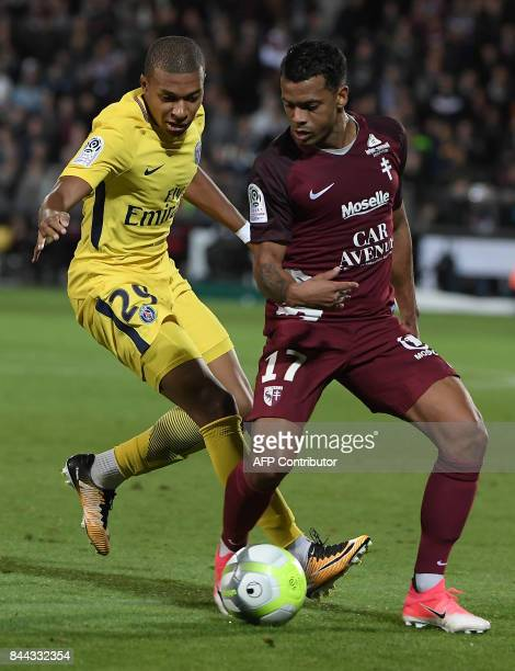 Paris SaintGermain's French forward Kylian Mbappe vies for the ball against Metz's FrenchTogolese forward Mathieu Dossevi during the French L1...