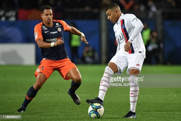 Paris Saint-Germain's French forward Kylian Mbappe vies with Montpellier's French defender Daniel Congre during the French L1 football match between...