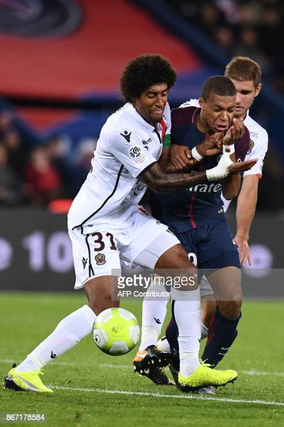 Paris SaintGermain's French forward Kylian Mbappe vies with Nice's Brazilian defender Dante during the French L1 football match between Paris...
