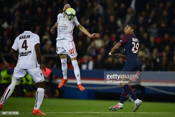 Paris SaintGermain's French forward Kylian Mbappe vies with Nice's French defender Christophe Jallet and Nice's Brazilian defender Santos Marlon...