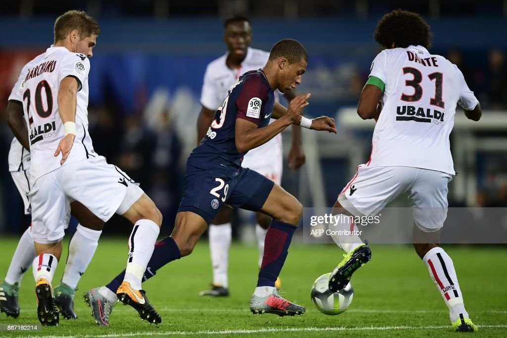Paris Saint-Germain's French forward Kylian Mbappe (C) vies with Nice's French defender Maxime Le Marchand (L) and Nice's Brazilian defender Dante during the French L1 football match between Paris Saint-Germain (PSG) and Nice (OGC Nice) on October 27, 2017, at the Parc des Princes stadium in Paris. / AFP PHOTO / Martin BUREAU