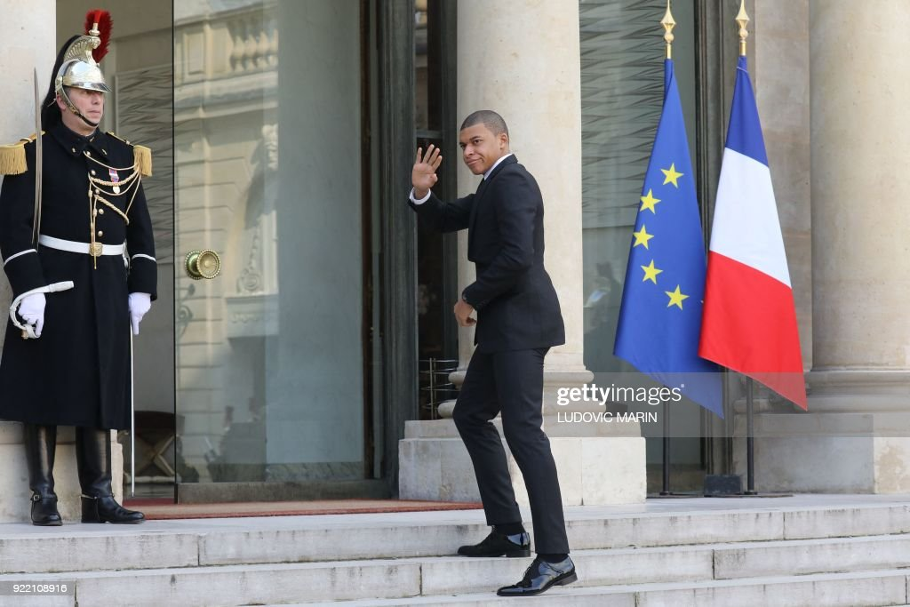 Paris Saint-Germain's French forward Kylian Mbappe waves as he arrives at the Elysee presidential palace, for a lunch with French President and Liberian President and other guests, on February 21, 2018, in Paris. /