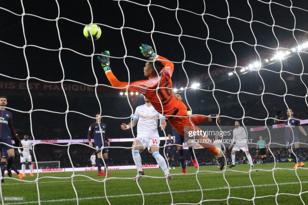 Paris Saint-Germain's French goalkeeper Alphonse Areola (C) dives for the ball during the French L1 football match between Paris Saint-Germain (PSG) and Marseille (OM) at the Parc des Princes in Paris on February 25, 2018. / AFP PHOTO / Geoffroy VAN