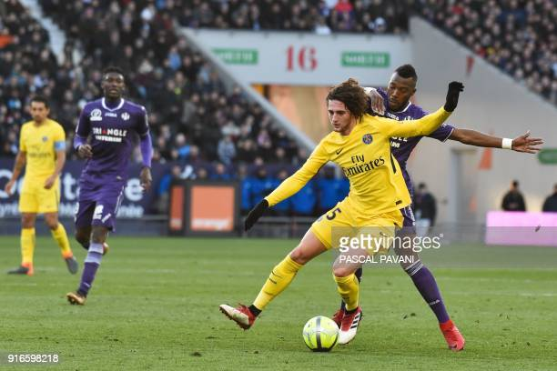 Paris Saint-Germain's French midfielder Adrien Rabiot holds off Toulouse's French forward Yaya Sanogo during the French L1 football match between...