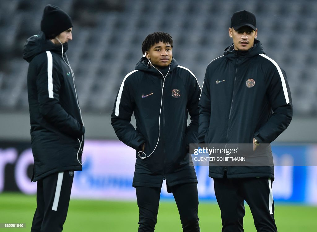 Paris Saint-Germain's French midfielder Adrien Rabiot (L), Paris Saint-Germain's French midfielder Christopher Nkunku (C) and Paris Saint-Germain's French keeper Alphonse Areola (R) walk on the pitch one day ahead of the UEFA Champions League Group B match between FC Bayern Munich vs PSG Paris, at the Allianz Arena in Munich, southern Germany, on December 4, 2017. /