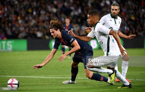 Paris Saint-Germain's French midfielder Adrien Rabiot vies for the ball with Saint-Etienne's French forward Kevin Monnet-Paquet during the French L1...