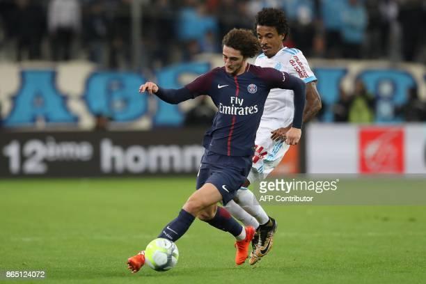 Paris SaintGermain's French midfielder Adrien Rabiot vies for the ball with Marseille's Brazilian midfielder Luiz Gustavo during the French L1...