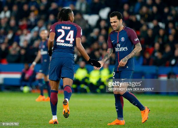 Paris SaintGermain's French midfielder Christopher Nkunku and Paris SaintGermain's Brazilian defender Daniel Alves touch hands during the French...