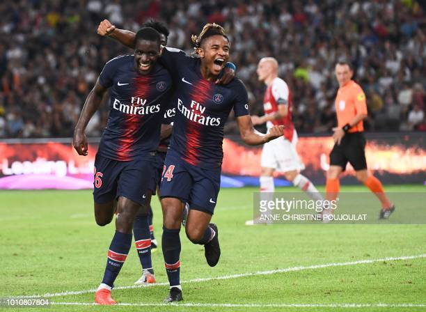 Paris SaintGermain's French midfielder Christopher Nkunku celebrates with Paris SaintGermain's defender Stanley Pierre N'Soki after scoring a goal...