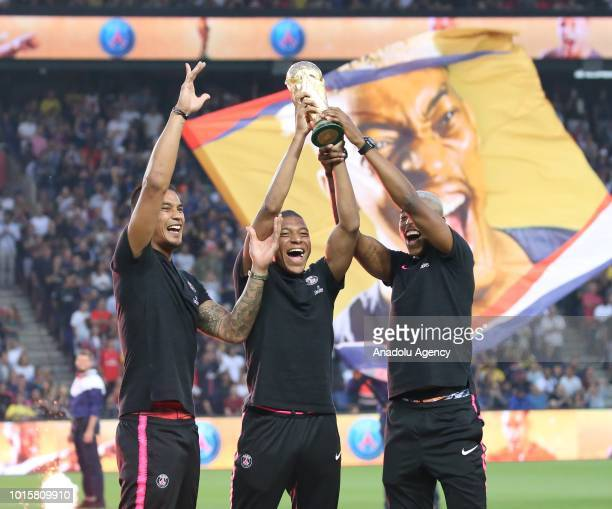 Paris SaintGermain's French national team players Alphonse Areola Kylian Mbappe and Presnel Kimpembe pose with the 2018 World Cup Trophy prior to the...