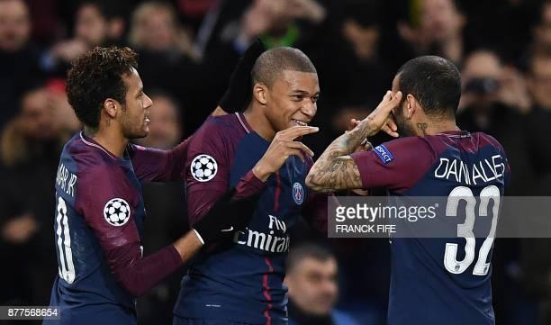 Paris SaintGermain's French striker Kylian Mbappe celebrates with teammates Brazilian striker Neymar and Brazilian defender Dani Alves after scoring...