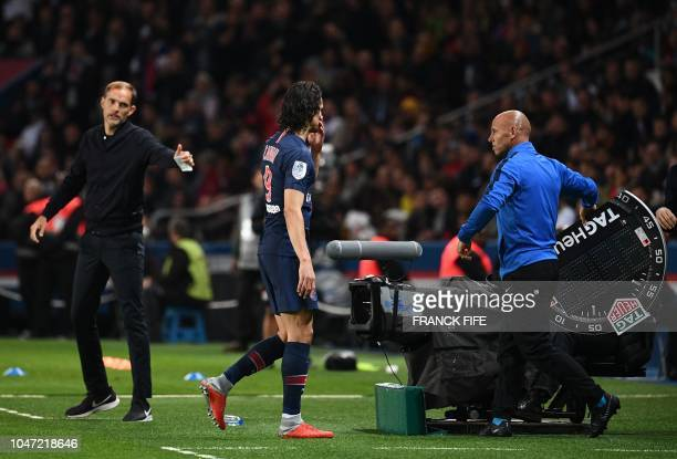 Paris SaintGermain's German coach Thomas Tuchel talks to Paris SaintGermain's Uruguayan forward Edinson Cavani as he leaves for substitution during...