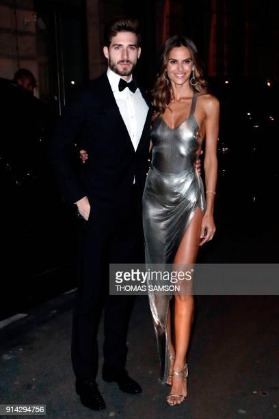 Paris SaintGermain's German goalkeeper Kevin Trapp and girlfriend Brazilian model Izabel Goulart pose as they arrive at the Pavillon Cambon in Paris...