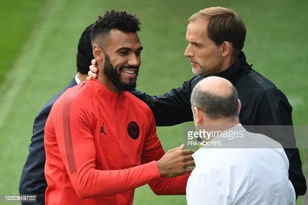 Paris SaintGermain's German head coach Thomas Tuchel reacts next to Paris SaintGermain's Cameroonian forward EricMaxim ChoupoMoting before a training...