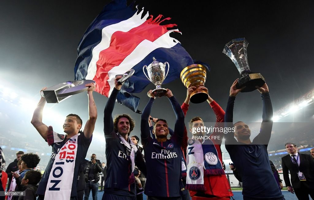Paris Saint-Germain's German midfielder Julian Draxler, Paris Saint-Germain's French midfielder Adrien Rabiot, Paris Saint-Germain's Brazilian defender Thiago Silva, Paris Saint-Germain's German goalkeeper Kevin Trapp and Paris Saint-Germain's French defender Layvin Kurzawa celebrate with a trophy after winning the French L1 title at the end of the French L1 football match Paris Saint-Germain (PSG) vs Rennes on May 12, 2018 at the Parc des Princes stadium in Paris.