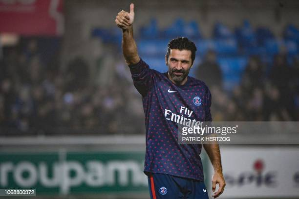 Paris SaintGermain's Italian goalkeeper Gianluigi Buffon gestures as he arrives on the football pitch for a warm up session prior to the French L1...