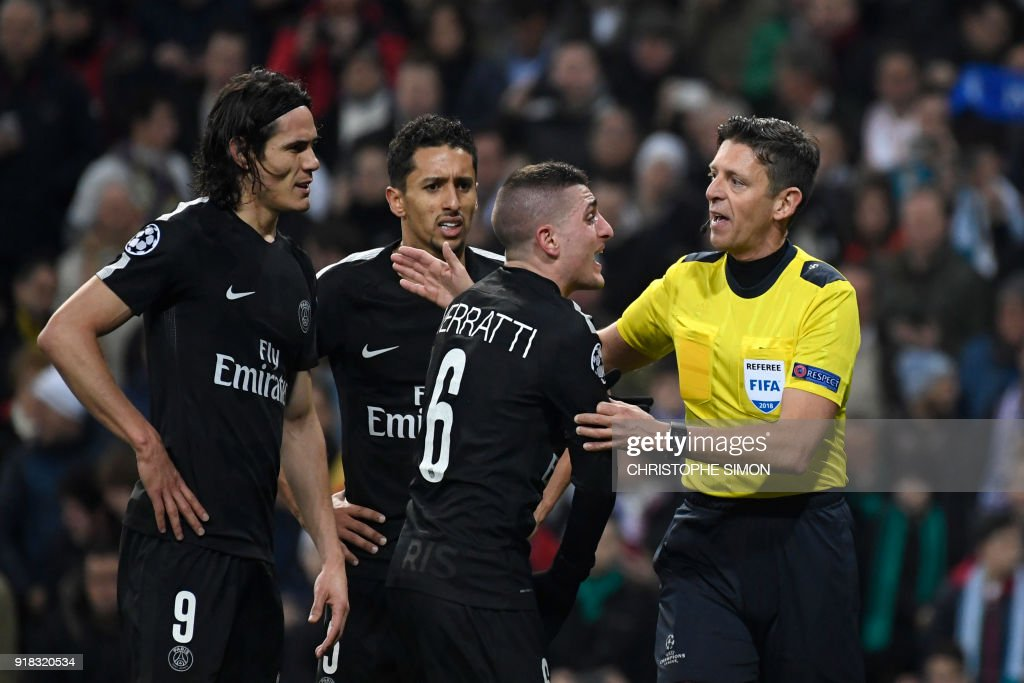 TOPSHOT - Paris Saint-Germain's Italian midfielder Marco Verratti (2R) complains to Italian referee Gianluca Rocchi (R) next to Paris Saint-Germain's Uruguayan forward Edinson Cavani (L) and Paris Saint-Germain's Brazilian defender Marquinhos during the UEFA Champions League round of sixteen first leg football match Real Madrid CF against Paris Saint-Germain (PSG) at the Santiago Bernabeu stadium in Madrid on February 14, 2018. /