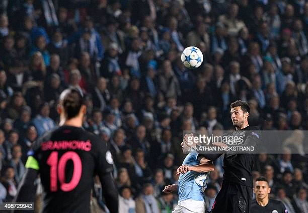 Paris SaintGermain`s Italian midfielder Thiago Motta and Malmo's Serbian forward Nikola Djurdjic jump for a header during the UEFA Champions League...