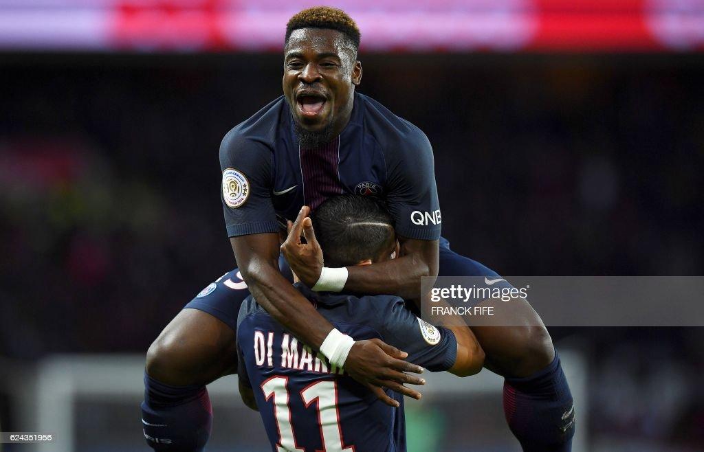TOPSHOT - Paris Saint-Germain's Ivorian defender Serge Aurier (Top) congratulates Paris Saint-Germain's Argentinian forward Angel Di Maria after he scored a goal during the French L1 football match between Paris Saint-Germain and Nantes at the Parc des Princes stadium in Paris on November 19, 2016. /