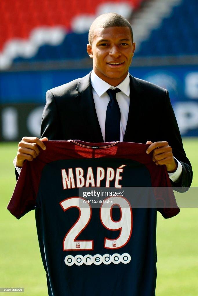 best service 1da8a c1003 Paris Saint-Germain's new forward Kylian Mbappe holds his ...