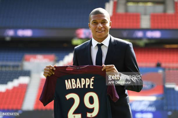 Paris Saint-Germain's new forward Kylian Mbappe holds his jersey during his presentation at the Parc des Princes stadium in Paris on September 6,...