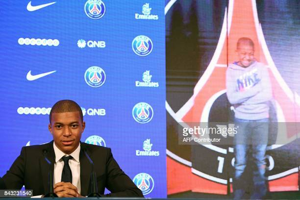 Paris SaintGermain's new forward Kylian Mbappe is pictured next to a childhood photo of himself in front of a PSG logo as he speaks during a press...
