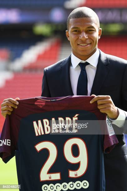 Paris Saint-Germain's new forward Kylian Mbappe poses with his jersey during his presentation at the Parc des Princes stadium in Paris on September...