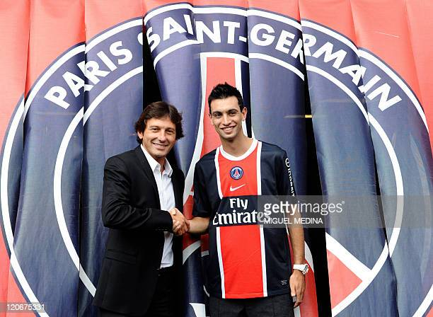 Paris SaintGermain's newly recruited Argentinian midfielder Javier Matias Pastore poses as he shakes hands with PSG's sporting director and former...