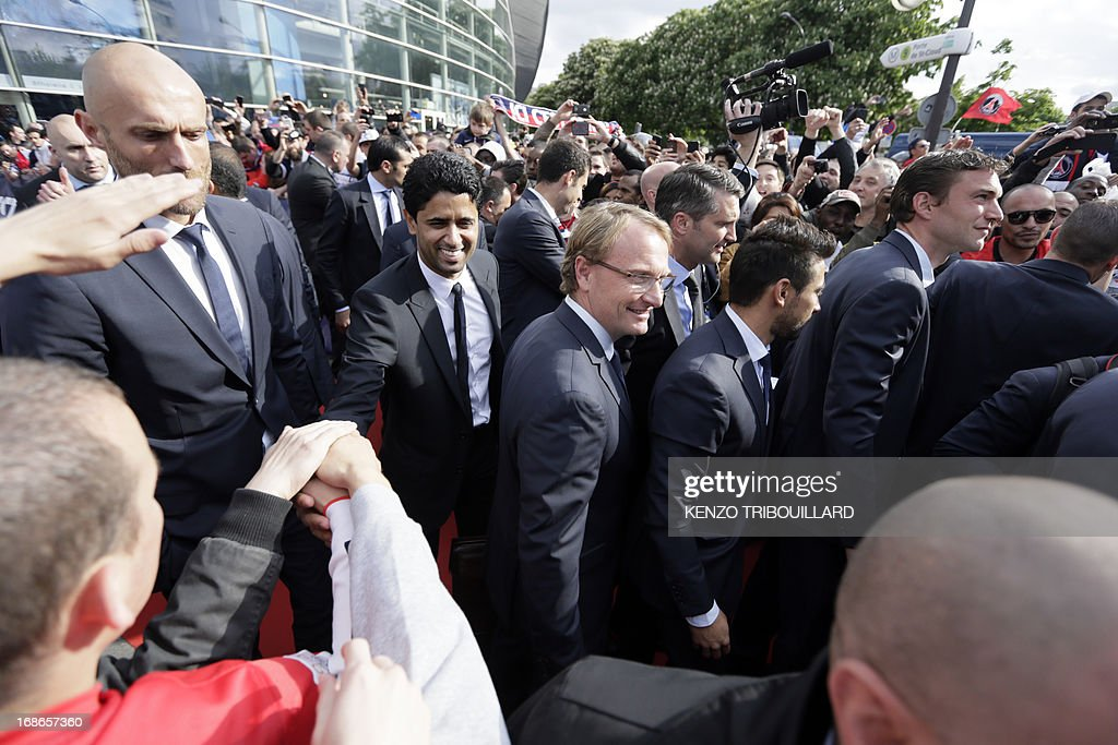 Paris Saint-Germain's owner and president Nasser Al-Khelaifi shakes hands with supporters as he arrives with the squad to parade in a double decker, on May 13, 2013 in Paris, one day after Paris secured French L1 football championship title.