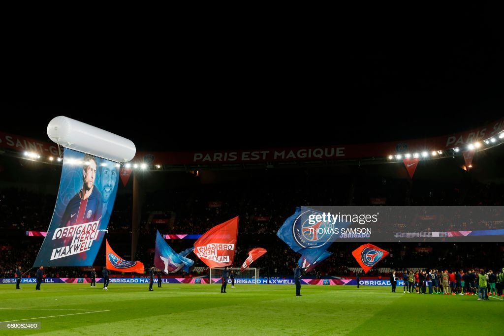 Paris Saint-Germain's players and supporters celebrate their teammate Brazilian defender Maxwell's last match with the team at the end of the French L1 football match between Paris Saint-Germain (PSG) and SM Caen on May 20, 2017 at the Parc des Princes stadium, in Paris. /