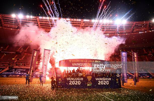 Paris Saint-Germain's players celebrate on the podium after winning the French League Cup final football match between Paris Saint-Germain and...