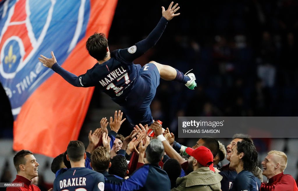 TOPSHOT - Paris Saint-Germain's players celebrate their teammate Brazilian defender Maxwell's last match with the team (up C), as they lift him the air at the end of the French L1 football match between Paris Saint-Germain (PSG) and SM Caen on May 20, 2017 at the Parc des Princes stadium, in Paris. /