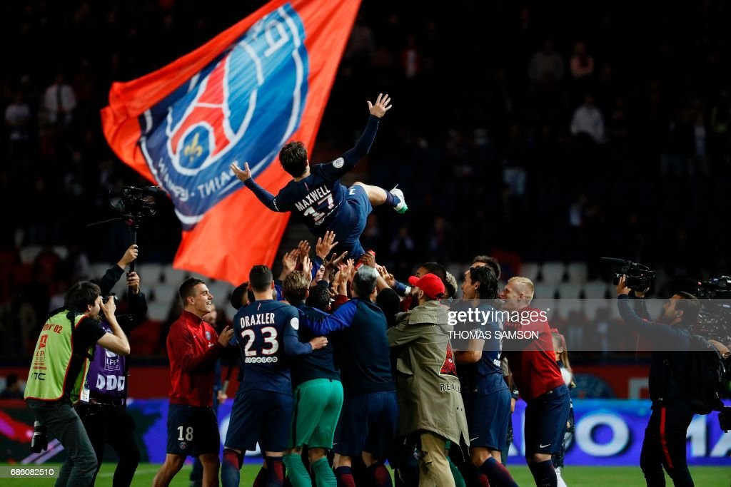 Paris Saint-Germain's players celebrate their teammate Brazilian defender Maxwell's last match with the team (up C), as they lift him the air at the end of the French L1 football match between Paris Saint-Germain (PSG) and SM Caen on May 20, 2017 at the Parc des Princes stadium, in Paris. /