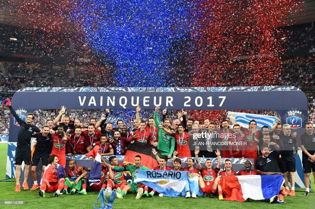 TOPSHOT - Paris Saint-Germain's players celebrate with the trophy after winning the French Cup final football match between Paris Saint-Germain (PSG) and Angers (SCO) on May 27, 2017, at the Stade de France in Saint-Denis, north of Paris. /