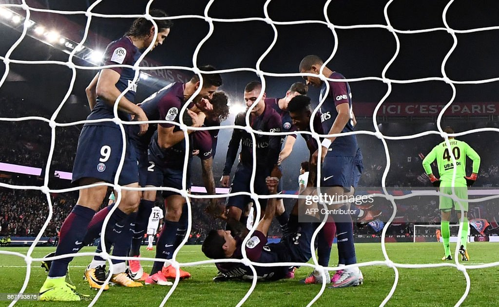 Paris Saint-Germain's players comfort Paris Saint-Germain's Argentinian midfielder Angel Di Maria (bottom) grimacing during the French L1 football match between Paris Saint-Germain (PSG) and Nice (OGC Nice) on October 27, 2017, at the Parc des Princes stadium in Paris. /