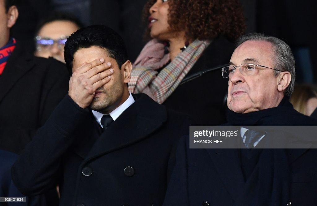 TOPSHOT - Paris Saint-Germain's Qatari president Nasser Al-Khelaifi (L) grimaces next to Real Madrid's Spanish president Florentino Perez as they attend the UEFA Champions League round of 16 second leg football match between Paris Saint-Germain (PSG) and Real Madrid on March 6, 2018, at the Parc des Princes stadium in Paris. /