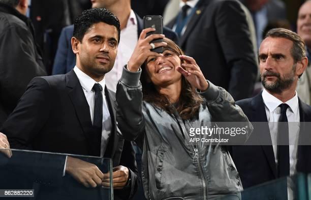Paris SaintGermain's Qatari president Nasser AlKhelaifi poses for a selfie with an unidentified person next to Paris SaintGermain's assistant general...
