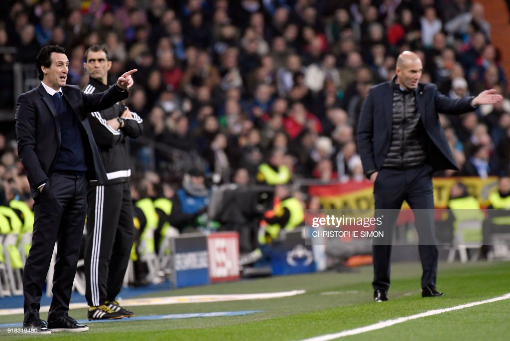 TOPSHOT - Paris Saint-Germain's Spanish coach Unai Emery (L) and Real Madrid's French coach Zinedine Zidane (R) gestures during the UEFA Champions League round of sixteen first leg football match Real Madrid CF against Paris Saint-Germain (PSG) at the Santiago Bernabeu stadium in Madrid on February 14, 2018. /