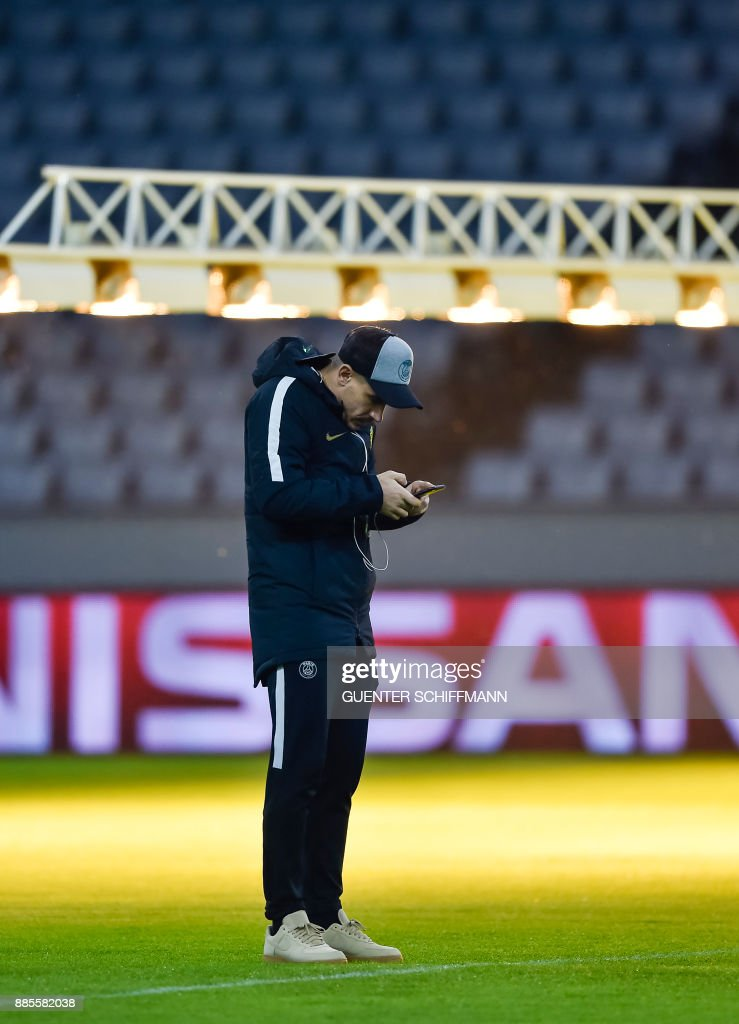 Paris Saint-Germain's Spanish defender Yuri Berchiche check his phone on the pitch one day ahead of the UEFA Champions League Group B match between FC Bayern Munich vs PSG Paris, at the Allianz Arena in Munich, southern Germany, on December 4, 2017. /