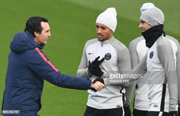 Paris SaintGermain's Spanish headcoach Unai Emery shakes hands with Paris SaintGermain's Argentinian forward Javier Pastore next to Paris...