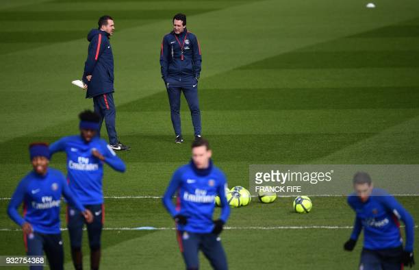 Paris SaintGermain's Spanish headcoach Unai Emery speaks with staff member as they watch players during a training session at SaintGermainenLaye...