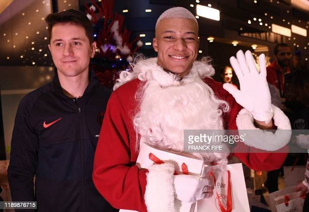Paris Saint-Germain's Spanish midfielder Ander Herrera and Paris Saint-Germain's French forward Kylian MBappe dressed as Santa Claus pose for a...