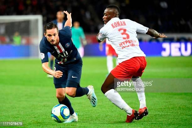 Paris Saint-Germain's Spanish midfielder Pablo Sarabia vies with Reims' Ivorian defender Ghislain Konan during the French L1 football match between...