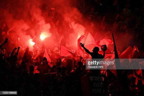 Paris Saint-Germain's supporters cheer and burn flares during the French L1 football match between Paris Saint-Germain and Saint-Etienne at the Parc...